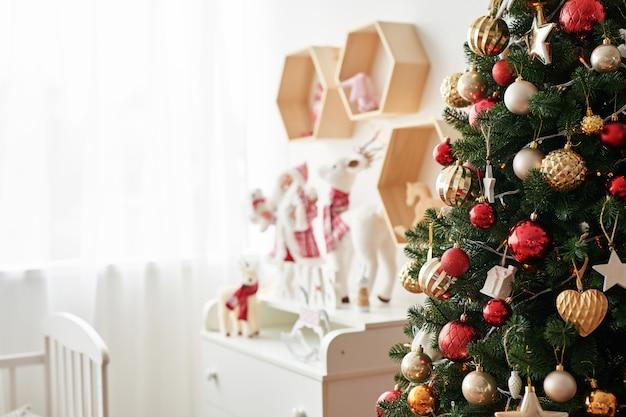 Półka z figurkami świątecznymi święty mikołaj i jeleń w pokoju dziecięcym. świąteczne wnętrze sypialni dziecięcej boże narodzenie w pokoju dziecinnym.