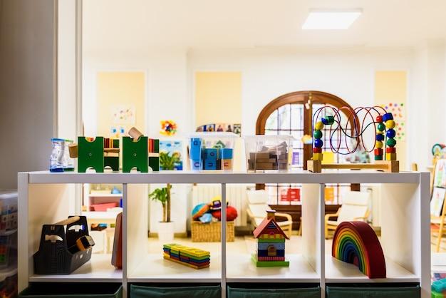 Półka z materiałami i grami w klasie dla dzieci.