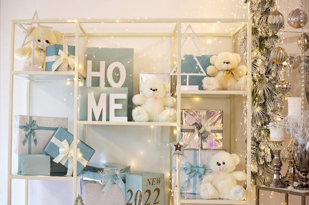 Półka z niebieskimi pudełkami prezentowymi i białymi misiami napis dom i nowy rok 2022