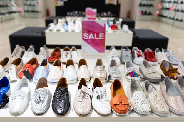 Półki z butami i botkami dla kobiet i znakiem sprzedaży