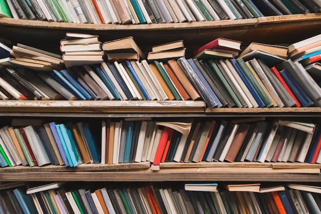 Półki ze starymi książkami w przytulnej bibliotece.