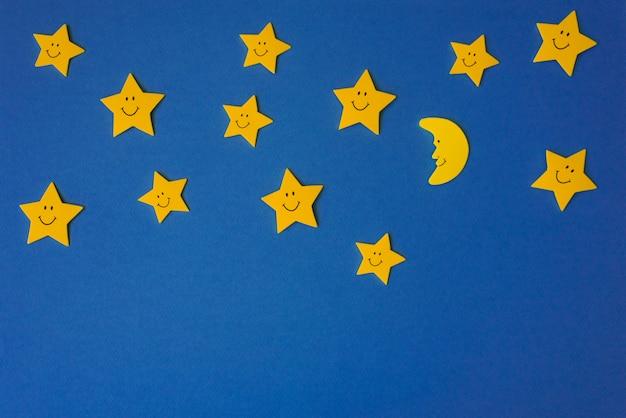 Półksiężyc i żółte gwiazdy na niebieskim nocnym niebie.