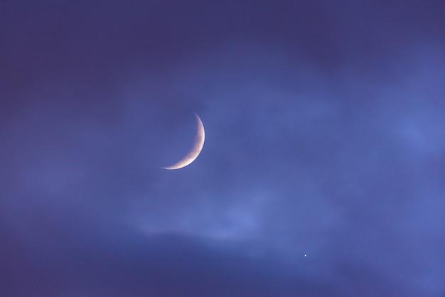 Półksiężyc nad chmurnym niebem przy zmierzchem obok wenus