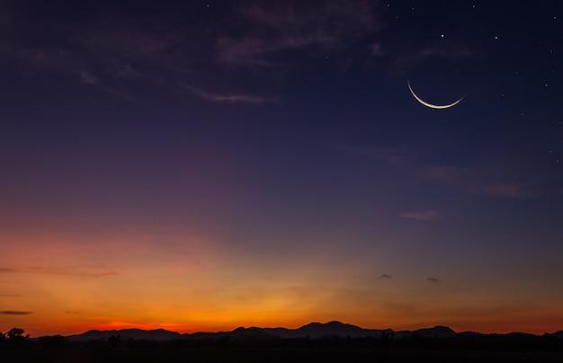 Półksiężyc wieczorem na ciemnoniebieskim niebie o zmierzchu