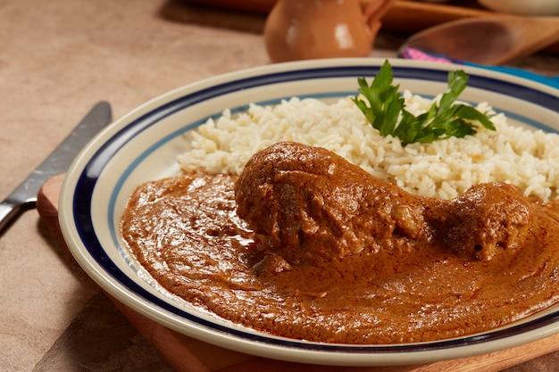 Pollo con pipiar rojo con arroz blanco comida mexicana
