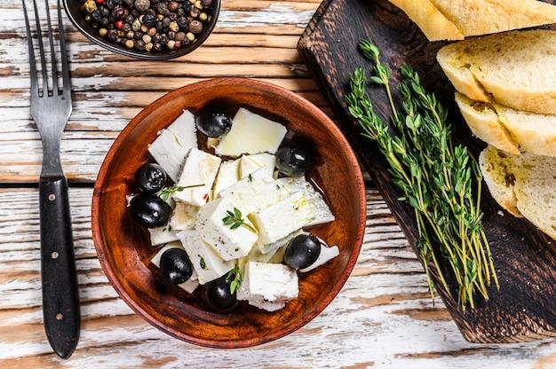 Półmisek antipasti ze świeżym serem feta, pieczywem i oliwkami. stół drewniany biały. widok z góry.