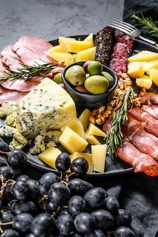 Półmisek antipasto z szynką, szynką parmeńską, salami, serem pleśniowym, mozzarellą i oliwkami. czarne tło. widok z góry