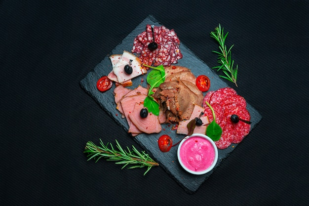 Półmisek antipasto zimne mięso z szynką prosciutto, kiełbasą, salami na desce łupkowej kamienia na tle marmuru. przystawka mięsna
