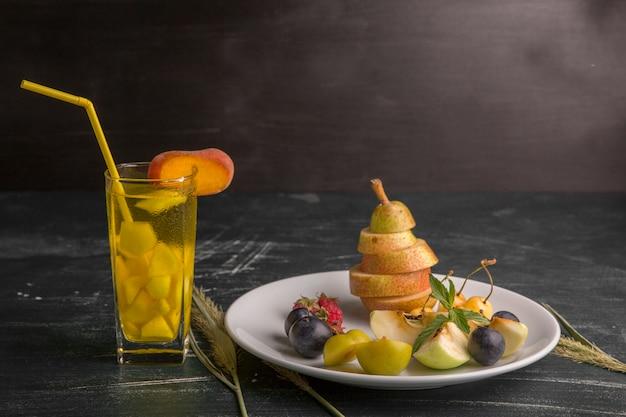 Półmisek białych owoców na białym tle na czarnej ścianie ze szklanką soku
