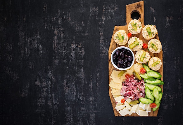Półmisek cateringowy antipasto z jamonem, serem, kanapką i czarnymi oliwkami na drewnianej desce. widok z góry, nad głową