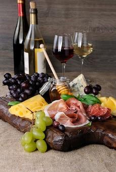 Półmisek cateringowy antipasto z suszonym bekonem prosciutto salami z serem i winogronami na drewnianym tle