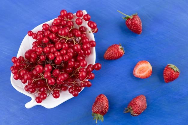 Półmisek czerwonych porzeczek z kilkoma porozrzucanymi truskawkami na niebieskim tle. wysokiej jakości zdjęcie