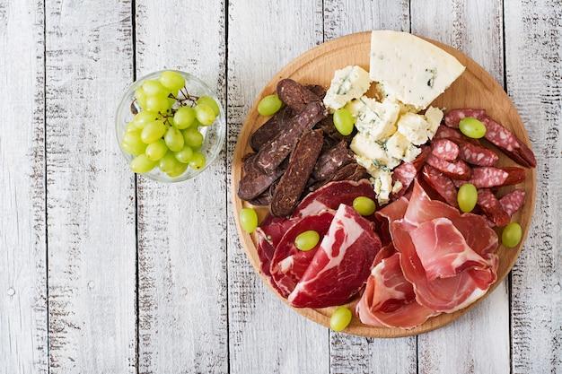 Półmisek gastronomiczny antipasto z boczkiem, suszonym serem, kiełbasą, serem pleśniowym i winogronami