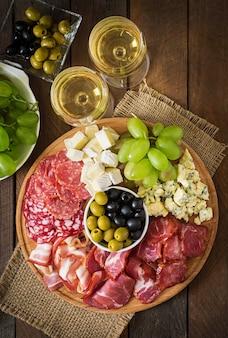 Półmisek gastronomiczny antipasto z boczkiem, suszonym serem, serem i winogronami
