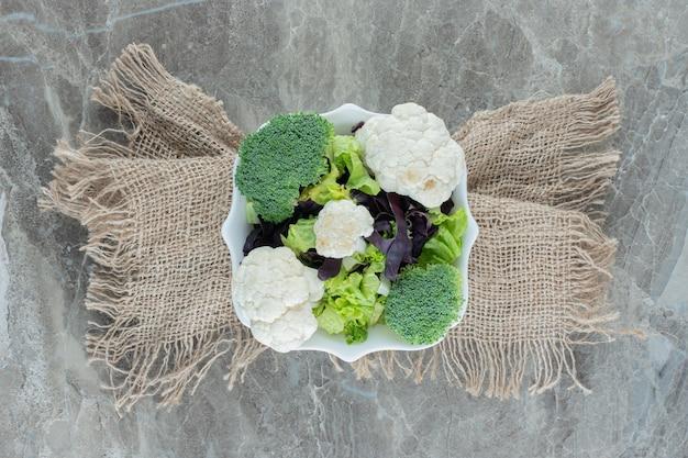 Półmisek kalafiora i brokułów na postumencie owiniętym tkaniną na marmurze.
