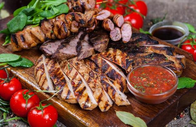 Półmisek mięs z grilla. różne pyszne grillowane mięso z warzywami. mieszane mięso z grilla z sosem pieprzowym i warzywami.
