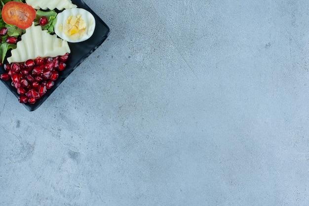 Półmisek owoców granatu, sera, jajka i plasterki pieprzu na marmurowej powierzchni