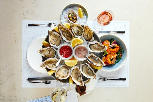 Półmisek owoców morza z otwartymi ostrygami z sosem i krewetkami