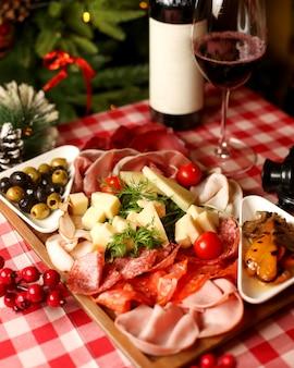 Półmisek przekąsek do wina z kiełbasami salami wędzonymi plasterkami mięsa, serem i oliwką