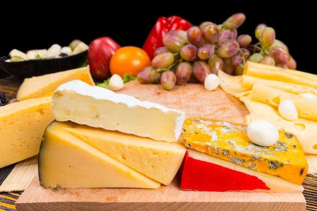 Półmisek serów z asortymentem serów w ćwiartkach, z kiścią świeżych winogron, pomidorem i słodką papryką