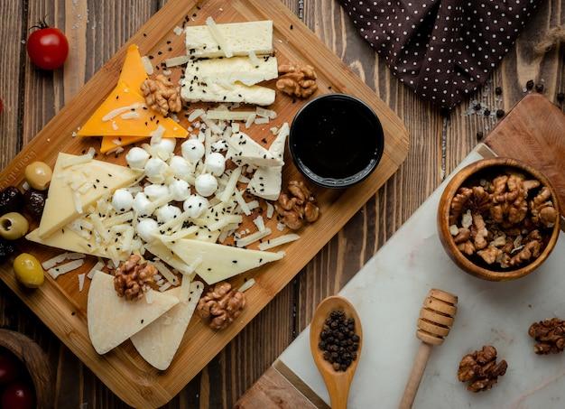Półmisek serów z oliwkami i orzechami włoskimi.