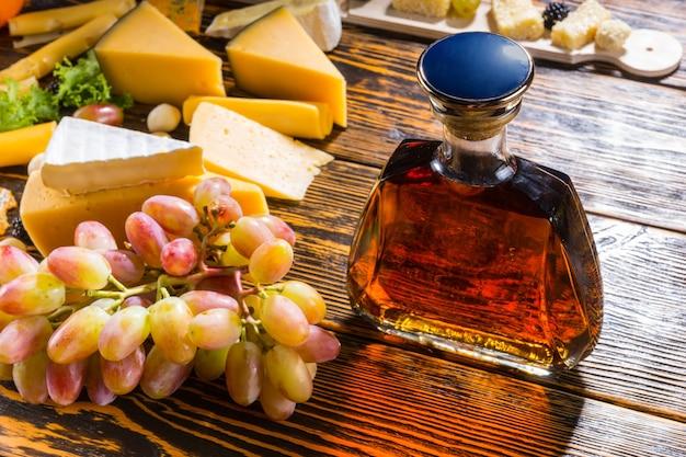 Półmisek serów z pysznym asortymentem wykwintnych serów, winogron i karafki brandy lub whisky stojącej na starym rustykalnym drewnianym stole w bufecie