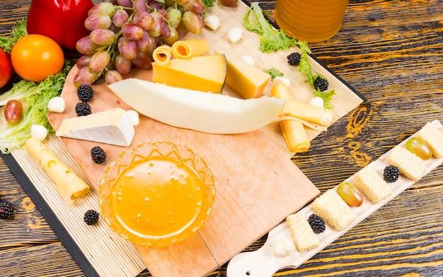Półmisek serów z różnymi rodzajami sera i miską maczanego miodu na drewnianym stole bufetowym ze świeżymi winogronami i pomidorami, widok z góry
