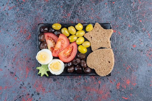 Półmisek śniadaniowy z pomidorami, oliwkami, jajkami i pieczywem.