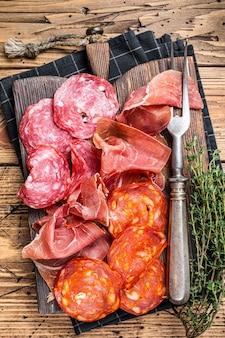 Półmisek wędlin podawany jako tradycyjne hiszpańskie tapas. salami, jamon, kiełbaski choriso na desce. drewniany stół . widok z góry.
