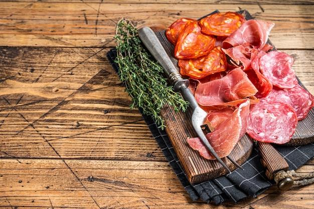 Półmisek wędlin podawany jako tradycyjne hiszpańskie tapas. salami, jamon, kiełbaski choriso na drewnianej desce. drewniane tła. widok z góry. skopiuj miejsce.