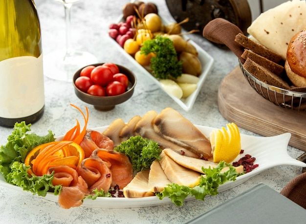 Półmisek wędzonego mięsa i łososia podany z marchewką i cytryną