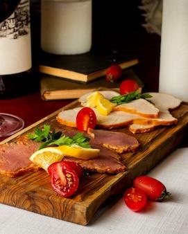 Półmisek wędzonego mięsa z wołowiną z indyka przyozdobionym pomidorami i cytryną