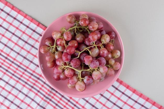 Półmisek winogron na ręczniku na marmurze