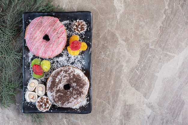 Półmisek z lokum, pączkami, szyszkami i marmoladami na marmurze.