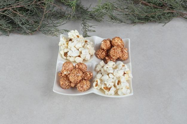 Półmisek z przekąskami wypełniony porcjami różnych rodzajów popcornu i wiecznie zielonych gałęzi drzew na marmurowym stole.
