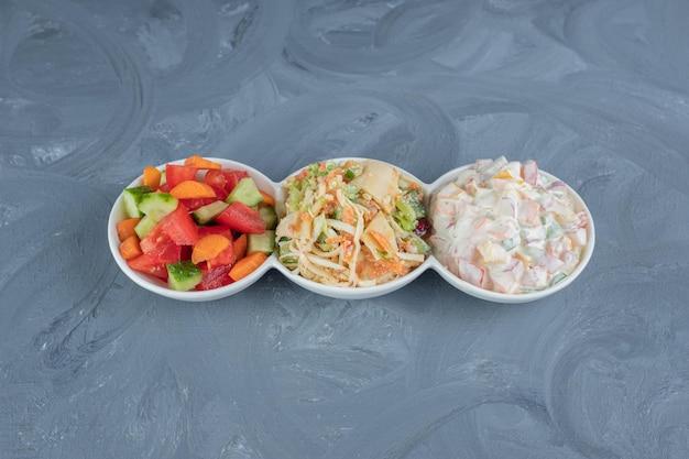 Półmisek zaopatrzony w porcje sałatek pasterskich, oliwkowych i mieszanych na marmurowym stole.