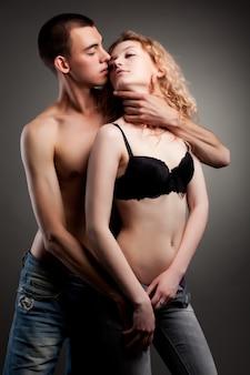 Półnaga młoda piękna para obejmująca się i przygotowująca się do seksu na szarym tle ściany
