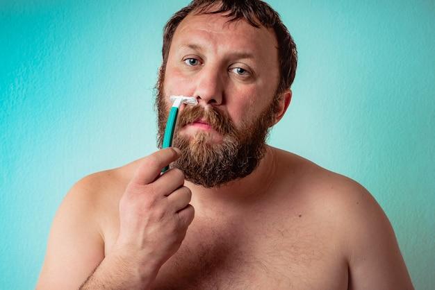 Półnagi kaukaski brodaty mężczyzna goli się z poważnym wyrazem twarzy