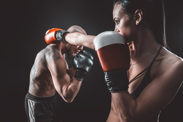 Półnagi kobieta ćwiczy z trenerem na lekcji boksu i samoobrony, studio, ciemna przestrzeń
