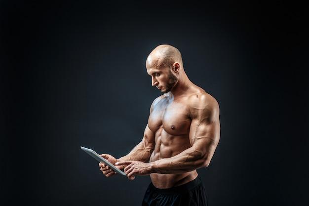Półnagi łysy mężczyzna za pomocą tabletu