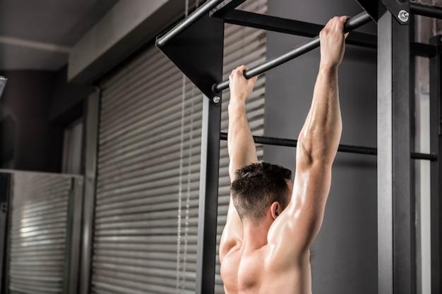 Półnagi mężczyzna robi ciągnąć na siłowni crossfit