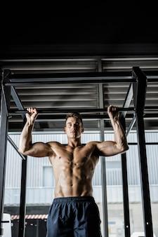 Półnagi mężczyzna robi ciągnąć na siłowni