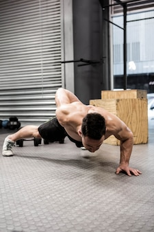 Półnagi mężczyzna robi push up na siłowni crossfit