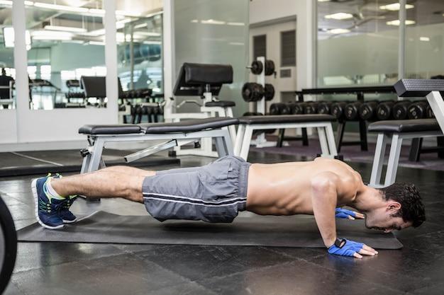 Półnagi mężczyzna robi push up na siłowni