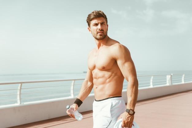 Półnagi mężczyzna robi wypracowania i różne ćwiczenia na świeżym powietrzu