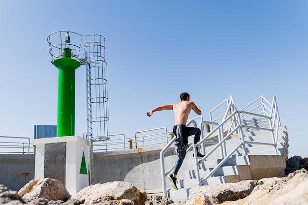 Półnagi mężczyzna skaczący po schodach w porcie z czystym niebem
