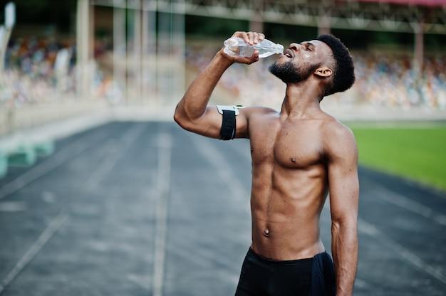 Półnagi mężczyzna sportowiec z pokrowcem na ramię do biegania na telefon komórkowy, postawiony na stadionie i woda pitna z butelki
