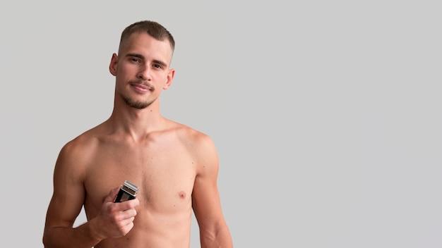 Półnagi mężczyzna trzyma golarkę elektryczną z miejsca na kopię