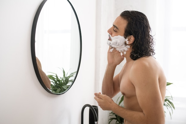 Półnagi muskularny mężczyzna, stosując piankę do golenia na twarzy, patrząc w lustro w łazience
