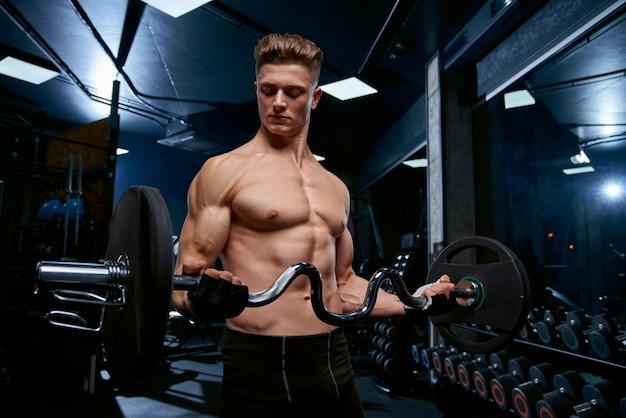 Półnagi sportowiec trenujący biceps ze sztangą.
